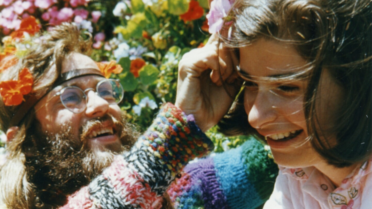 """A man places flowers into Penny Cooper's hair. 