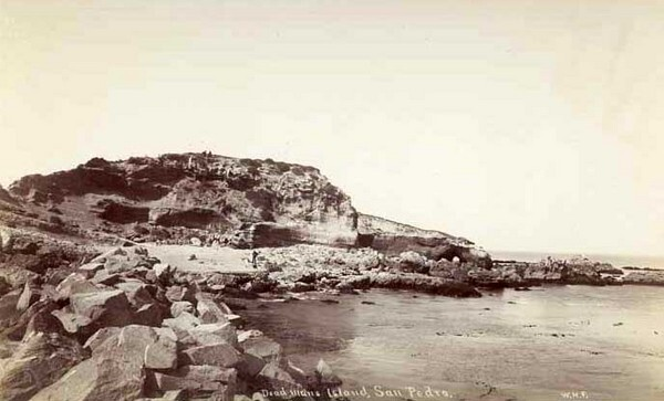 At low tide, visitors to Dead Man's Island could walk around a rocky beach. Circa 1895 photograph by W. H. Fletcher, courtesy of the California State Library.