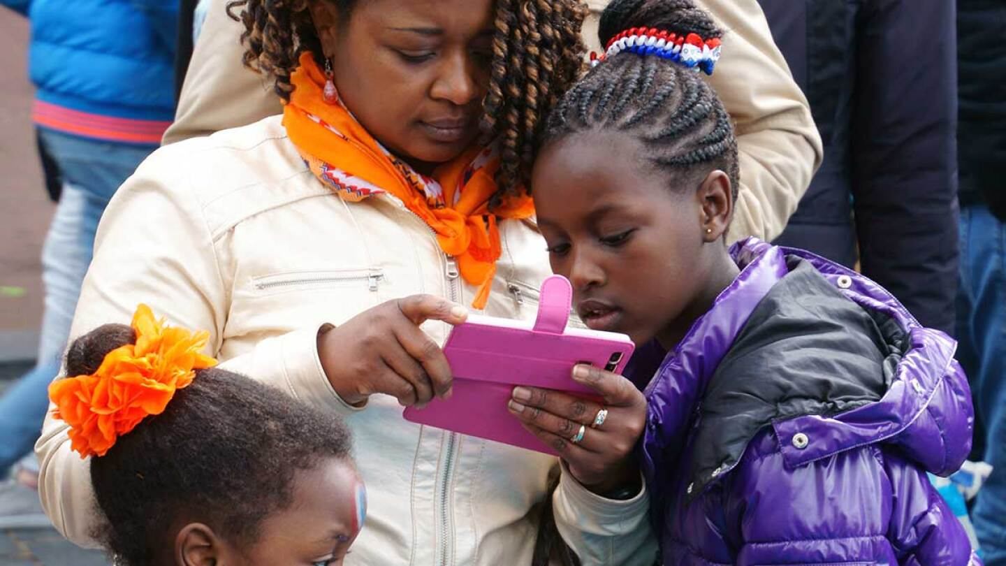 A young girl looks over her caregiver's cell phone.