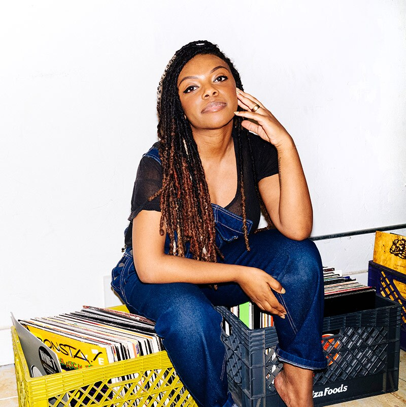 Jazzi McGilbert, founder of Reparations Club sits on boxes of records. | Daniel Redwood