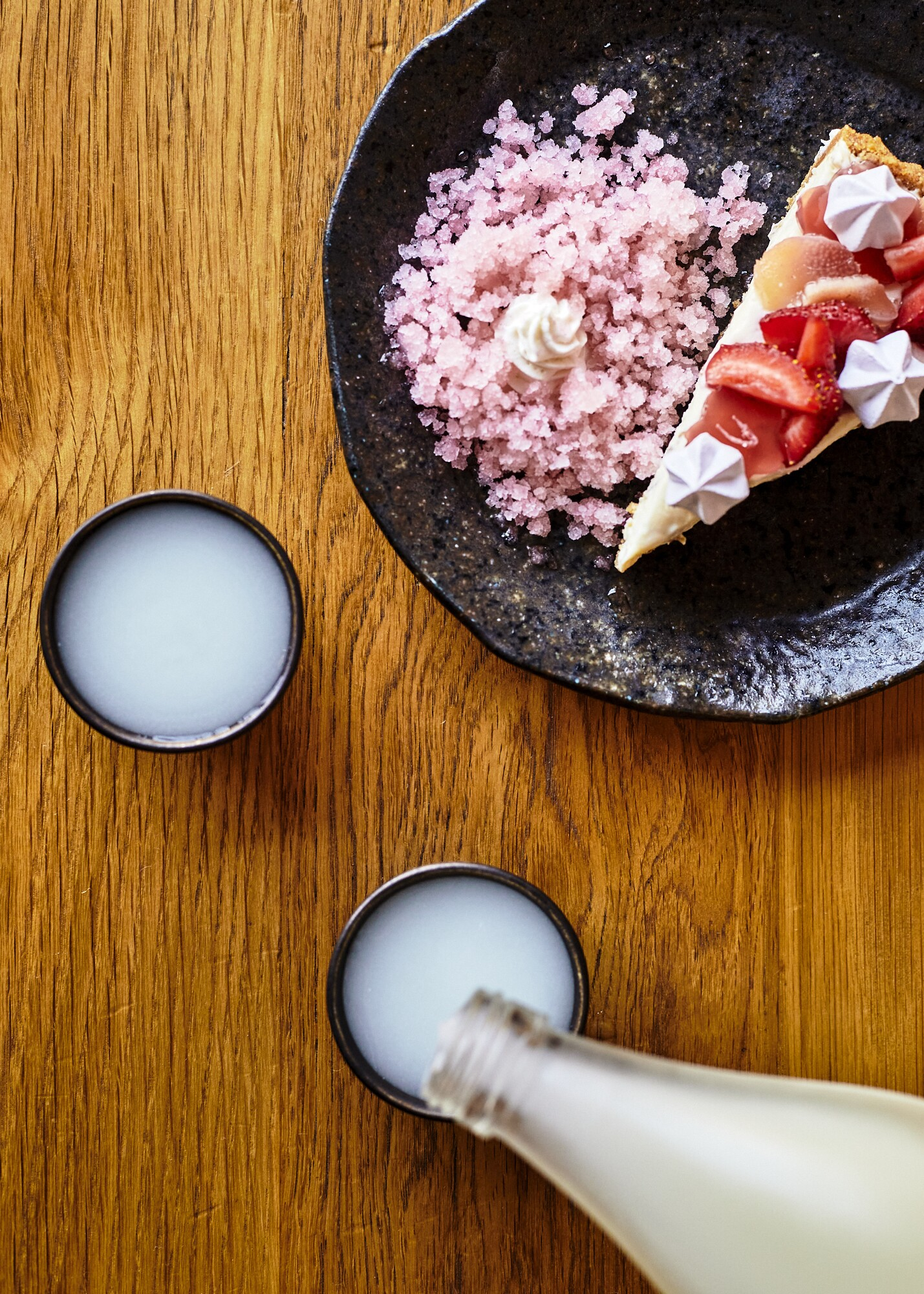 Cloudy nigori is poured in a cup beside a plate of ume cheesecake topped with strawberry rhubarb jellies, hibiscus meringue and red shiso granita.