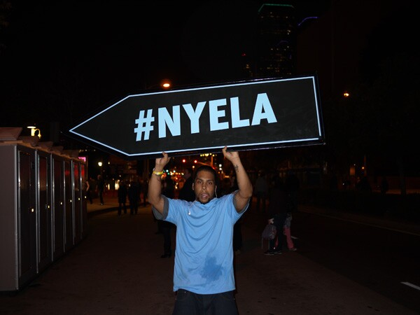 Sign carriers flip NYELA signs to direct people to sections of the park to participate in activities