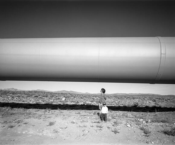 Walker and Ellen under LA Aqueduct, Owens Valley, CA, 1992. | Photo: Robert Dawson