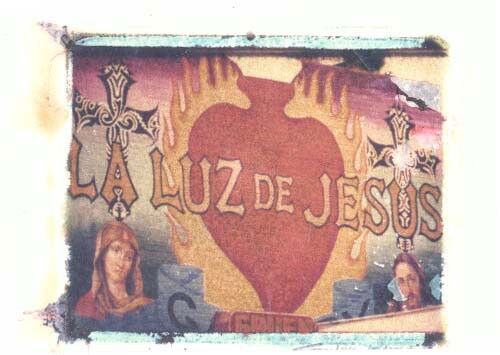 """A painting that reads """"La Luz de Jesus."""" Behind the text is a red shape with flames behind it."""