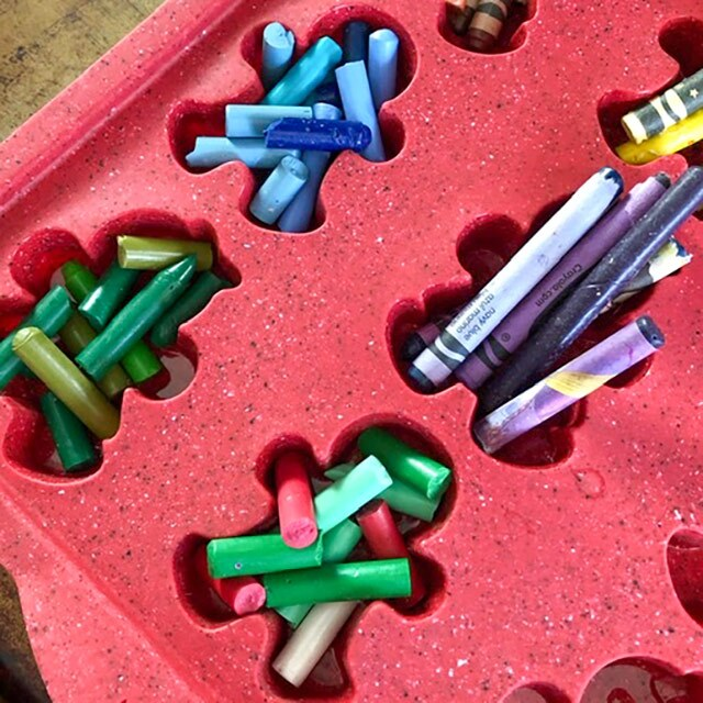 Pieces of crayons in a silicone baking tray with gingerbread doll shapes.