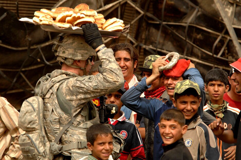 A group of Iraqi children look on as a U.S. Soldier practices balancing a plate of bread on his head in the Jameela market area of the Sadr City district of Baghdad, Iraq. | Tech. Sgt. Cohen A. Young / United States Forces Iraq/ Flickr