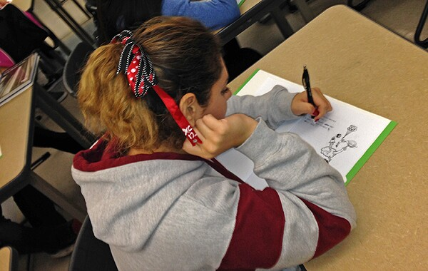 Student begins jotting ideas down in her Youth Voices Notebook