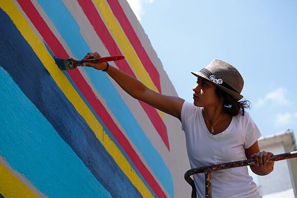 Kristy Sandoval applies detail to mural in Istanbul.   Photo: Mehmet Naci Demirkol.
