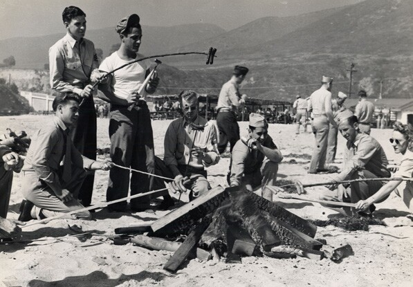 Photograph of Junamay Coffey and other Marines cooking over a campfire at Laguna Beach, 1945. On the backside Coffey wrote: Laguna Beach, CA, 1945.  Operation...46, Weiner Roast.
