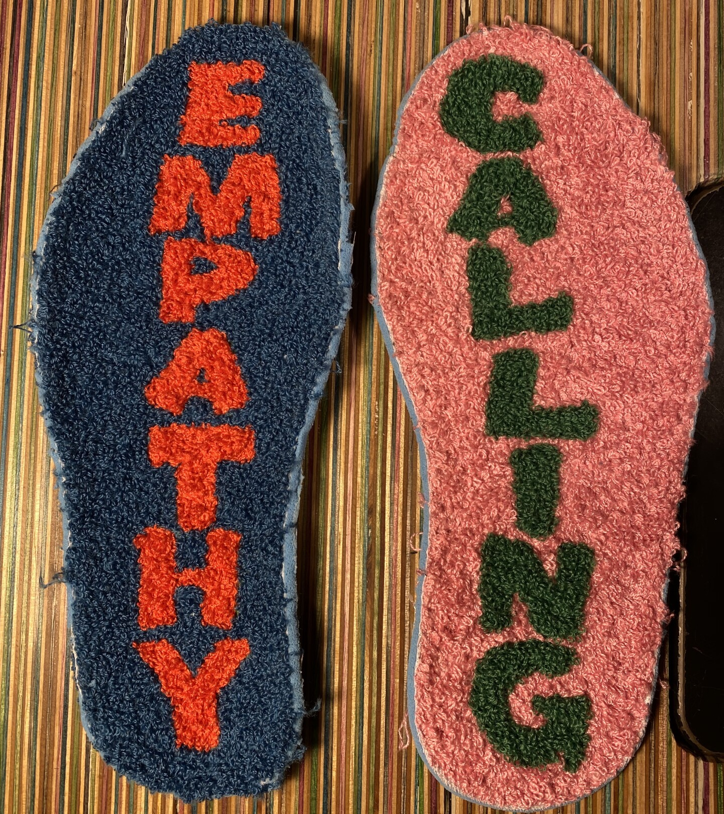 """Shoe soles chenille embroidered with the word """"Empathy"""" on the left sole and """"Calling"""" on the right sole. """"Empathy"""" is embroidered in a bright orange block text over a navy blue background. """"Calling"""" is embroidered in a forest green block text over a pink background."""