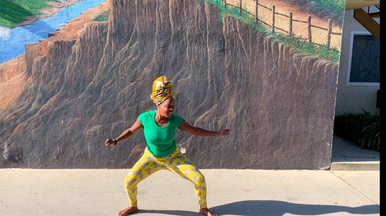 A young African American woman with a turban dances for one of Invertigo's Dance Care Package performances | Courtesy of Invertigo