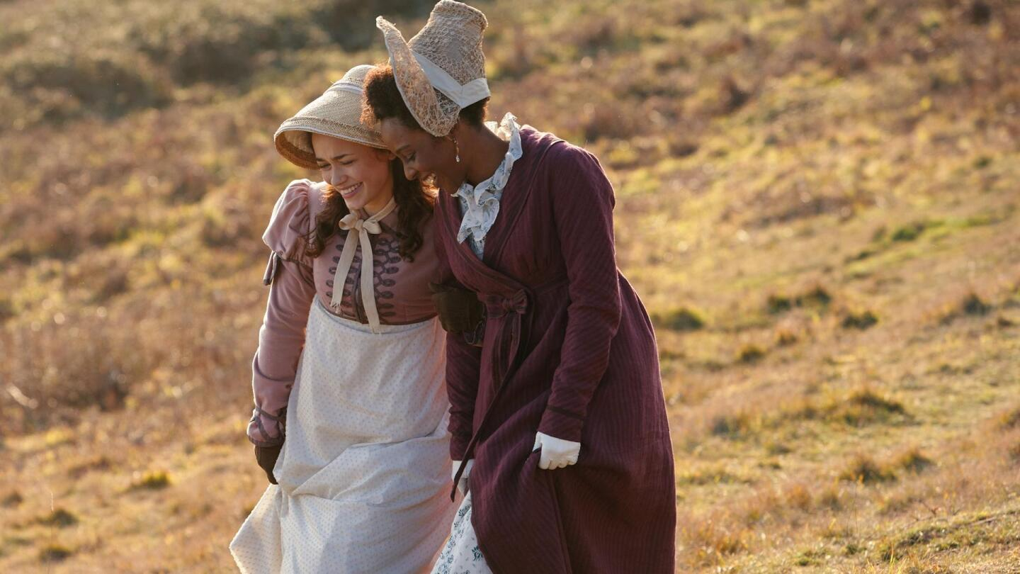 """Two women share laughter with each other. 