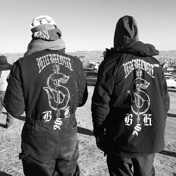 Artists Cannupa Hanska Luger and Jesse Hazelip at Oceti Sakowin Camp, Standing Rock. Luger's coveralls (left) will be on display at the Autry Museum.|  Photo: courtesy Cannupa Hanska Luger.