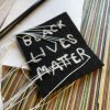 """A black, square-shaped piece of fabric with chain stitch embroidery reading the words, """"BLACK LIVES MATTER"""" in white thread. The ends of the threads are long and loose. The patch sits on top of a multicolored, striped surface."""