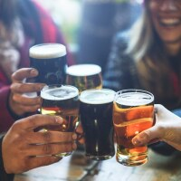 A group of friends drink beer together. | iStock via Getty Images