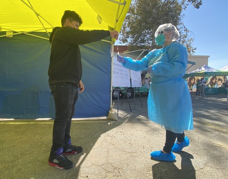 An L.A. Unified School District student drops a nasal swab from a COVID-19 test into a tube during a demonstration at San Fernando Middle School on Oct. 16, 2020.