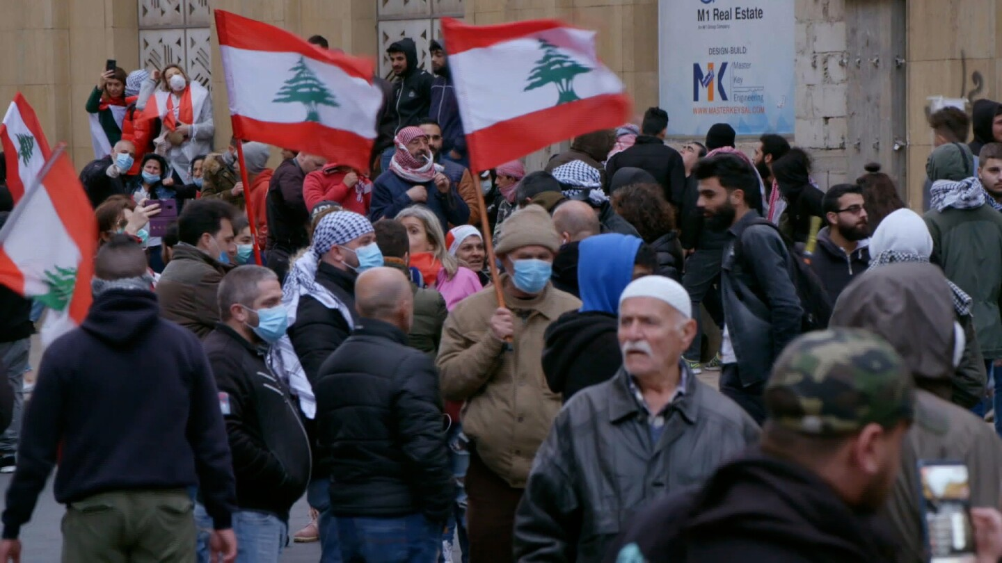 A crowd gathers on the street, some people holding up flags of Lebanon.