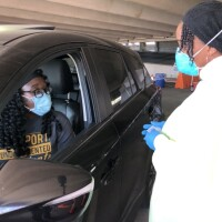 CSULB employee Fatou Olshanski confers with nurse Erica Olauge about a vaccine at a drive-through clinic in a parking structure at Cal State Long Beach.