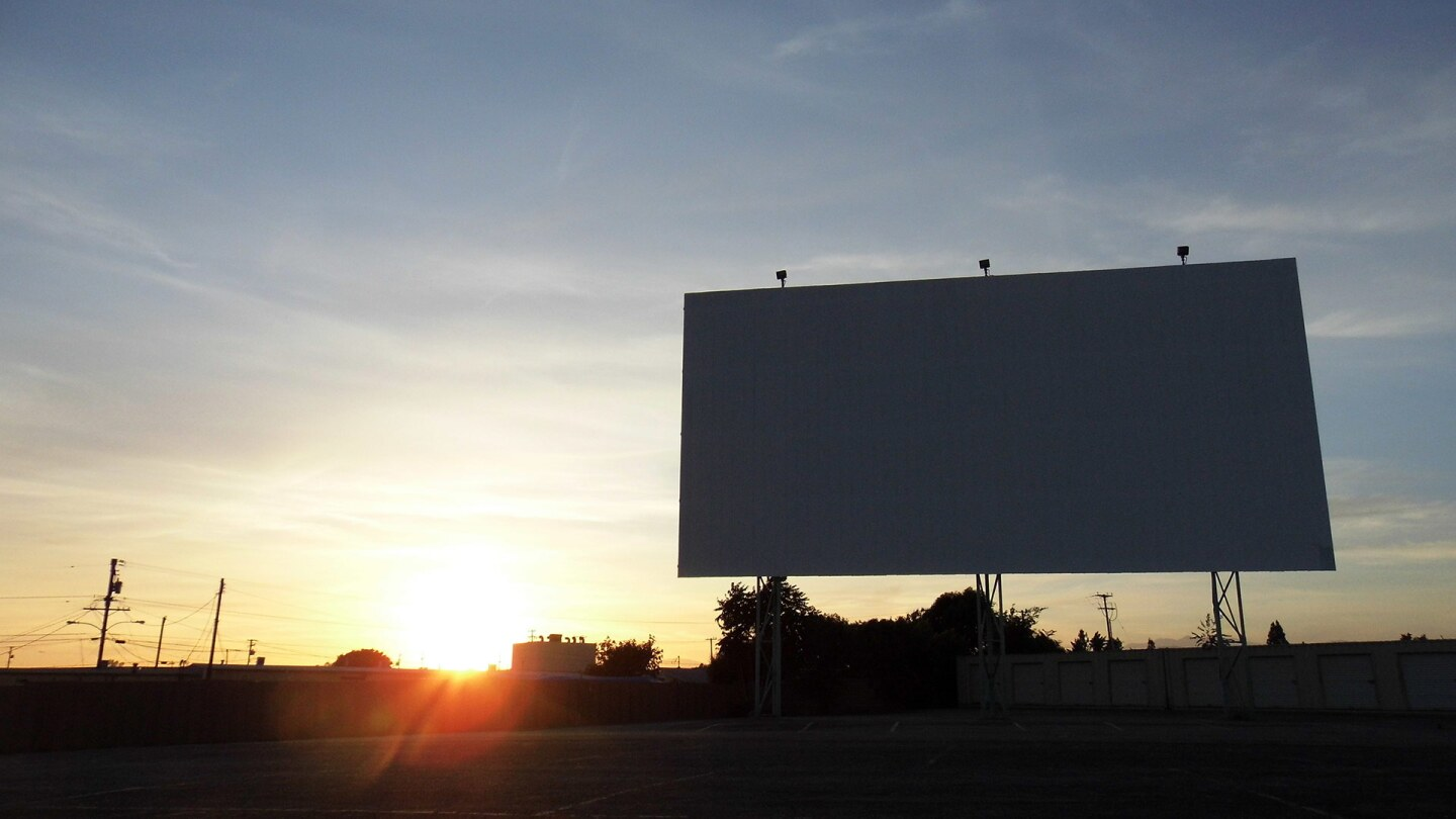 A blank drive-in screen at sunset