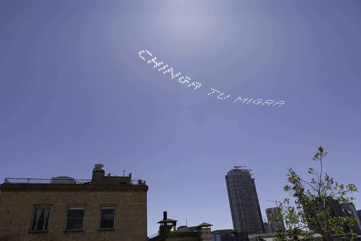 """""""CHINGA TU MIGRA"""" written in in the sky, contributed by Yosimar Reyes, over the L.A. Metropolitan Jail 