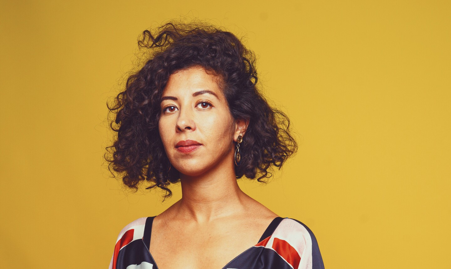 Filmmaker Assia Boundaoui stands in front of a yellow backdrop.