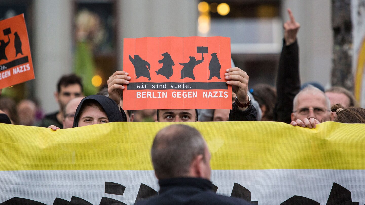 """Germany Decides: Counter demonstrator holding a sign reading """"Berlin against Nazis"""" at anti-Merkel rally."""