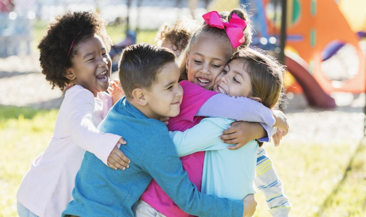 Four children hug each other.