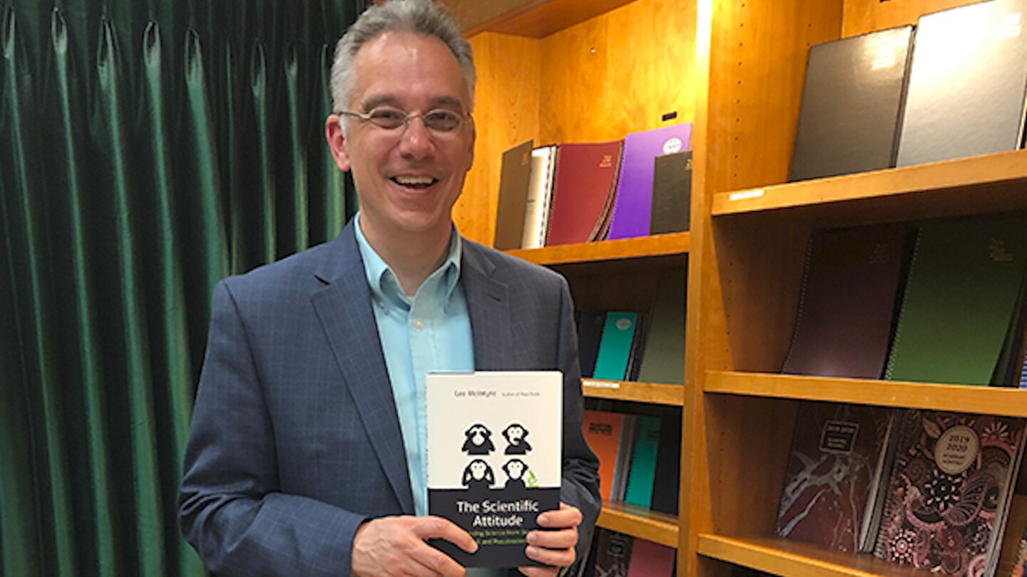 """Author Lee McIntyre poses with his book, """"The Scientific Attitude."""""""