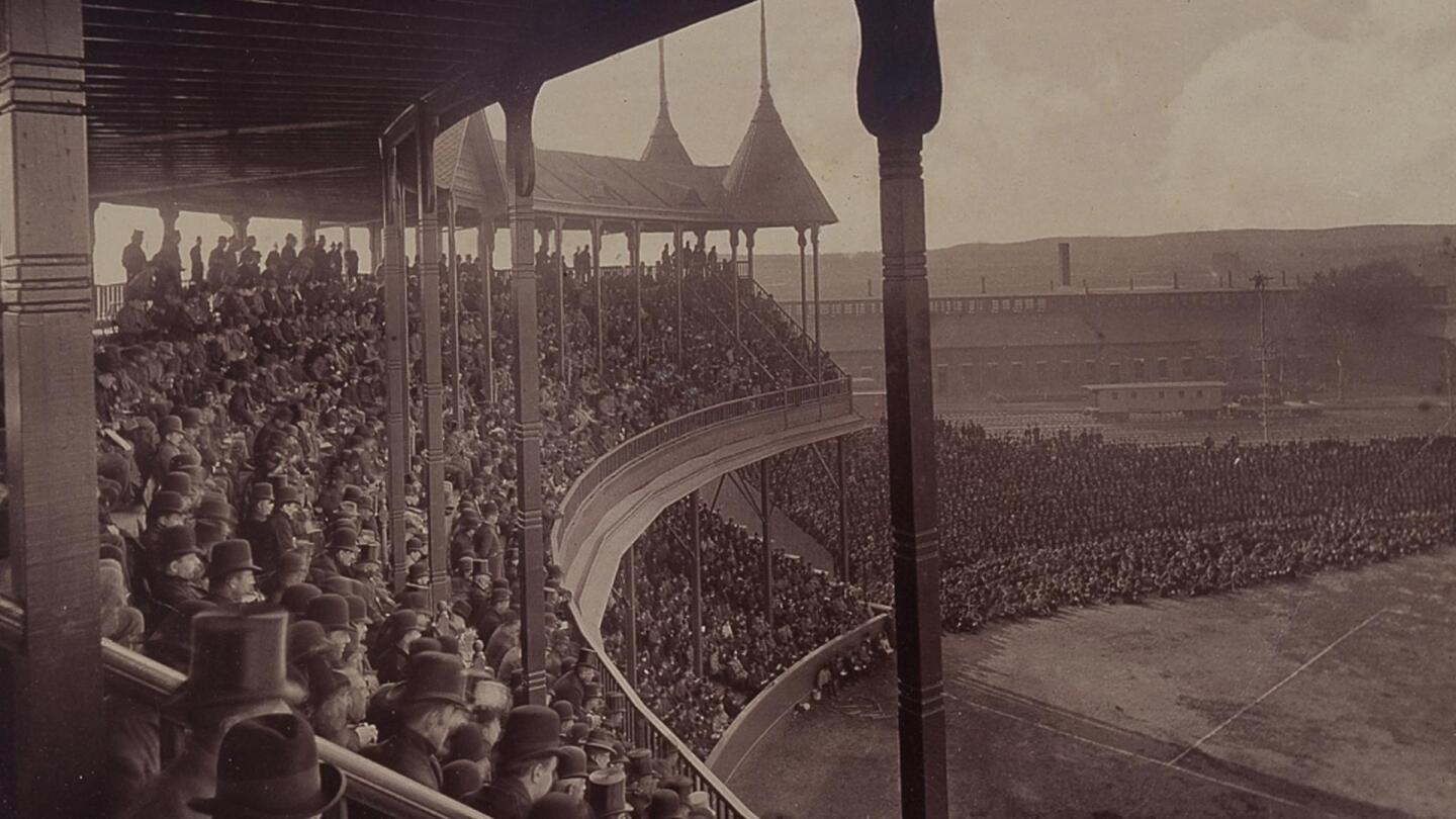 Many people sitting in the stands watching a baseball game.
