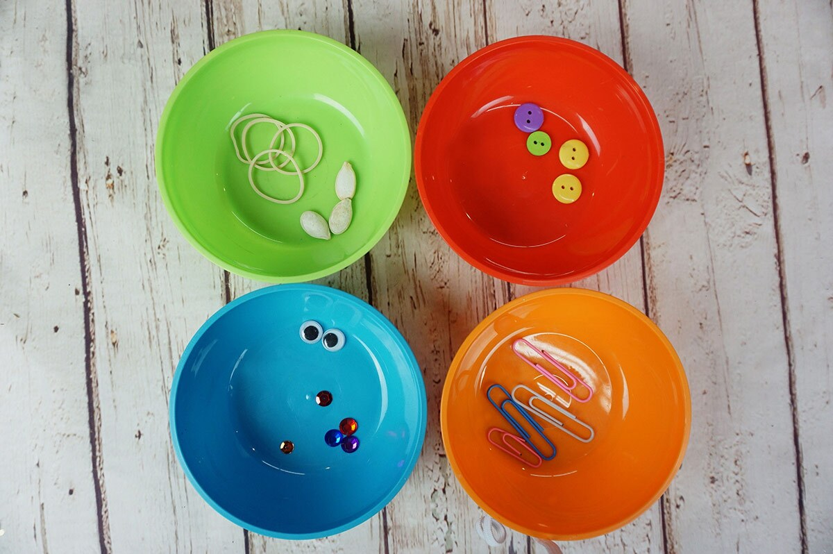 Four colorful bowls filled with items sorted by type including rubber bands, seeds, paper clips, buttons and sequins