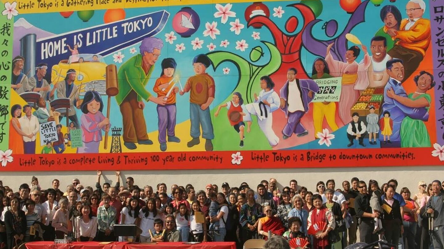 Dozens of people stand in front of a colorful mural depicting Japanese American history