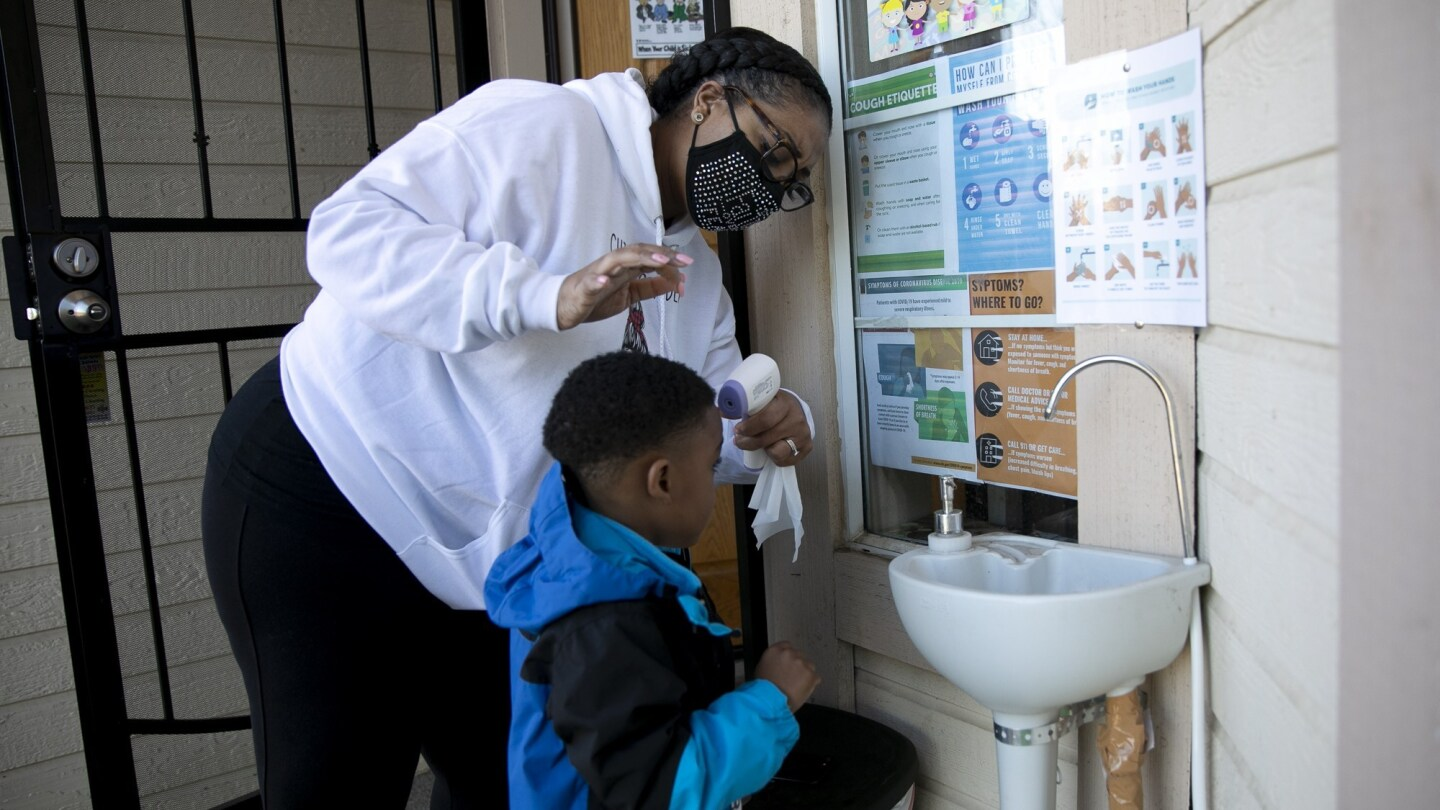 Family daycare provider Lucre-ce Lester takes a student's temperature as he arrives for the day at her home-based daycare in Antioch on February. 17, 2021.
