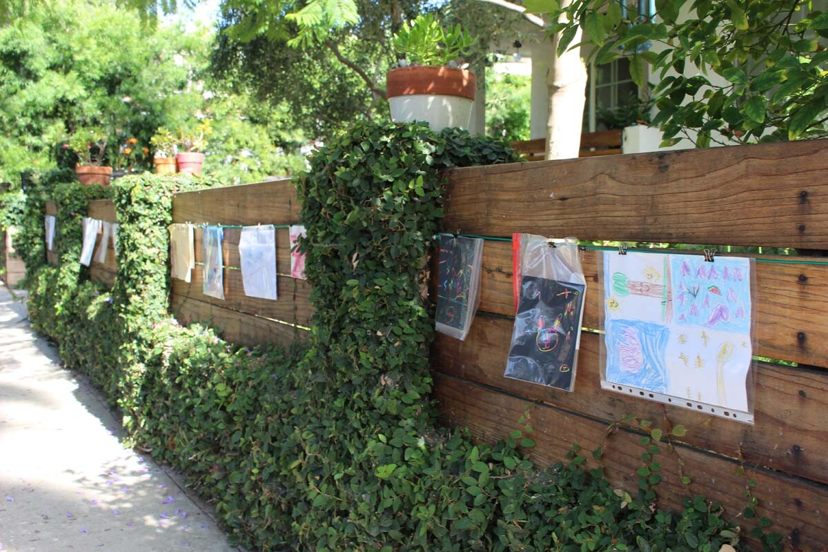 Detail of the children's artwork hanging from a cable on Dan Fields' Los Feliz fence gallery.