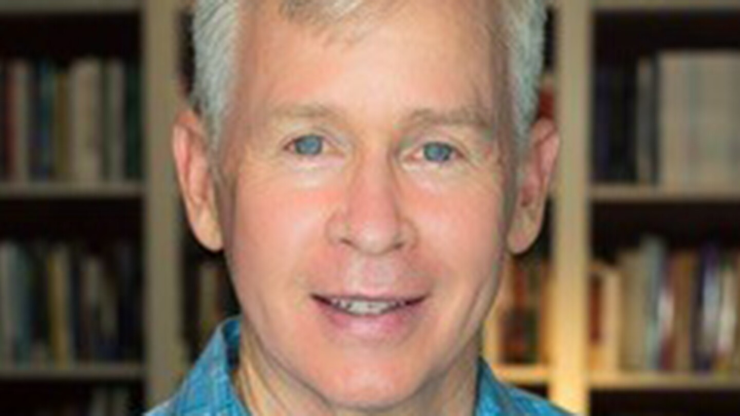 Dr. Philip Lance wears his white hair short. He is standing in front of a bookshelf and is wearing a blue plaid button down.