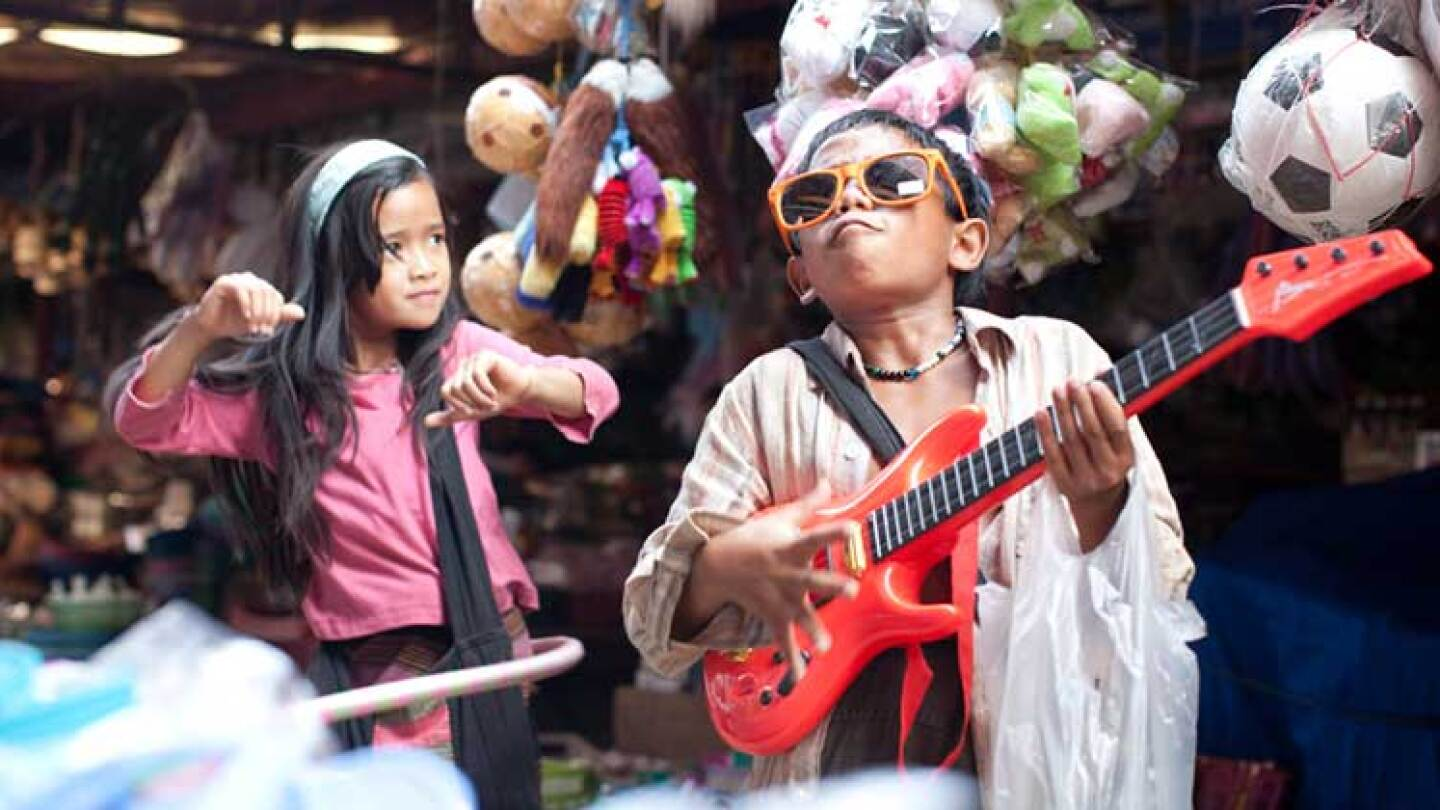 "Two young children, including a boy holding a guitar who does James Brown impersonations.  | Still from ""Rocket"""
