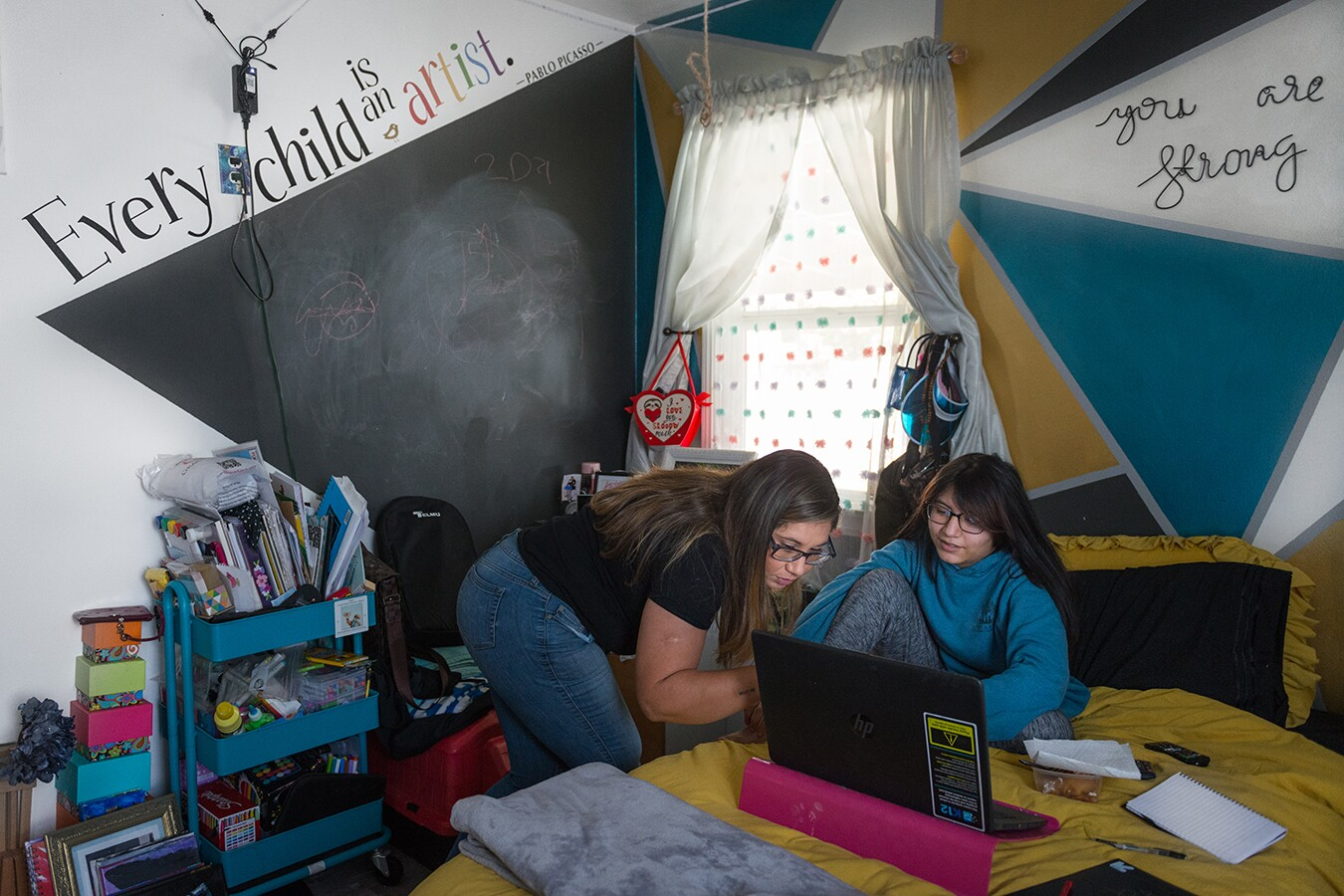 Rocio helps her daughter, Rhianna, with online classes. Rhianna sits on her bed, topped with a mustard yellow comforter and her laptop opened in front of her. The walls of her room are painted in a vibrant, geometric pattern. Along her wall are various school supplies, books and other miscellaneous items.