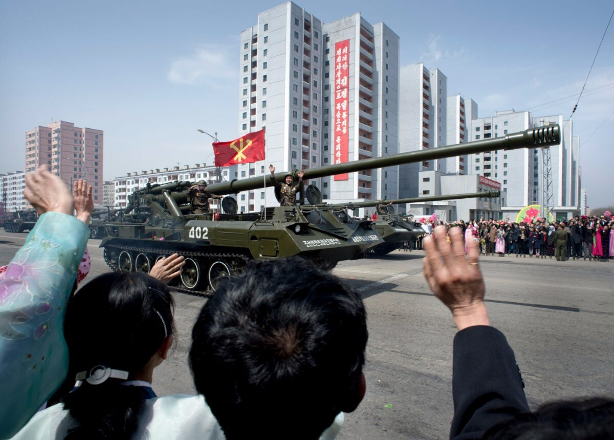 North Koreans wave to soldiers during a massive military parade celebrating the 100th anniversary of the birth of the country's founder Kim Il Sung. Pyongyang, North Korea   Mark Edward Harris