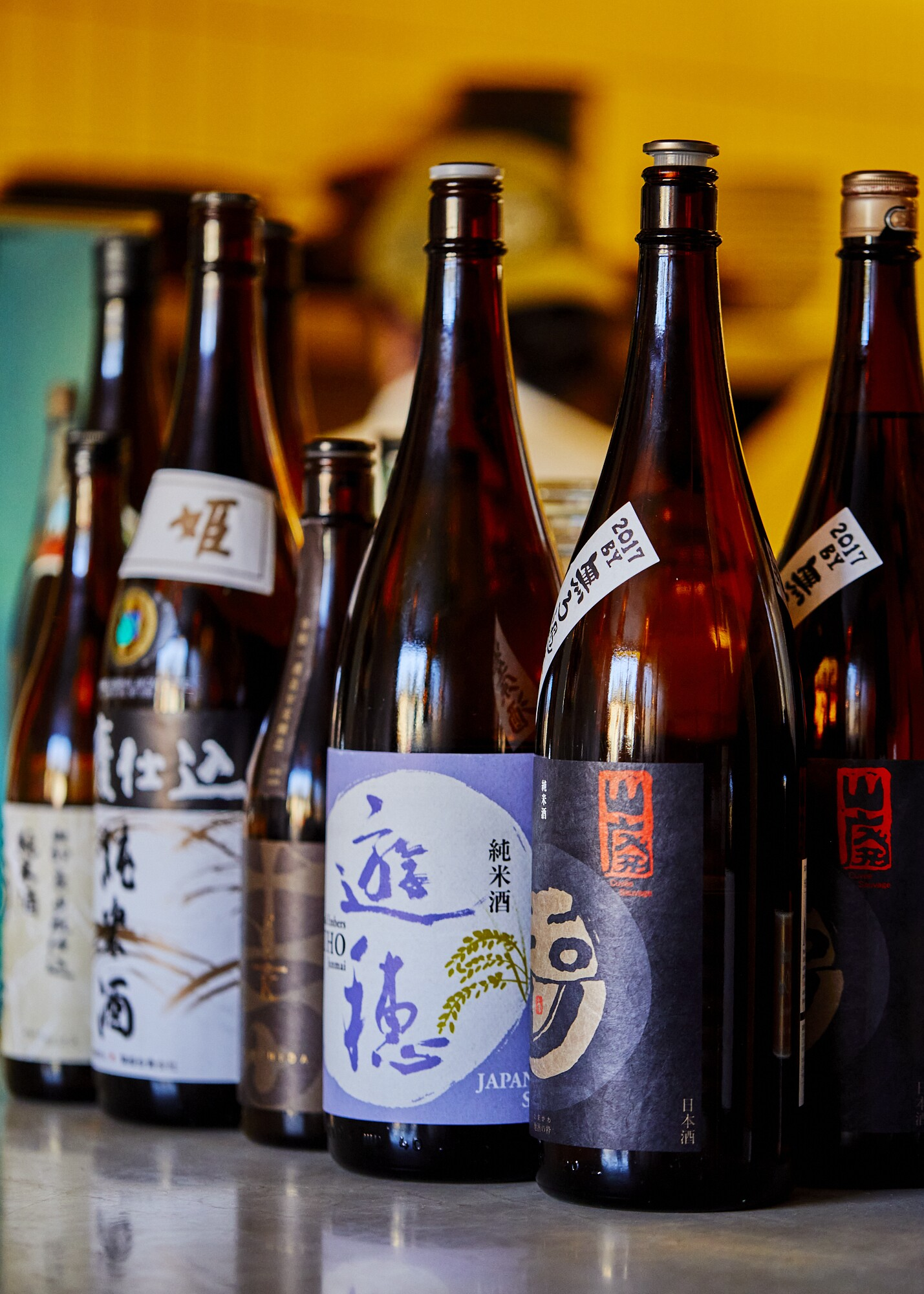 A selection of sake bottles set side by side.