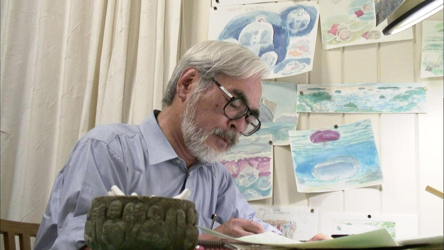 """Hayao Miyazaki looks down at a piece of paper in his hand on a desk. 