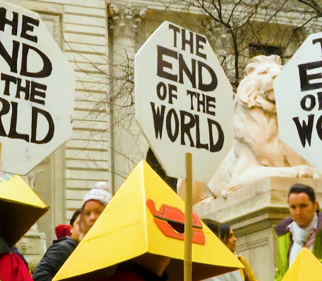 """Demonstrators wearing pyramidal head coverings hold up signs that read, """"The End of the World."""""""