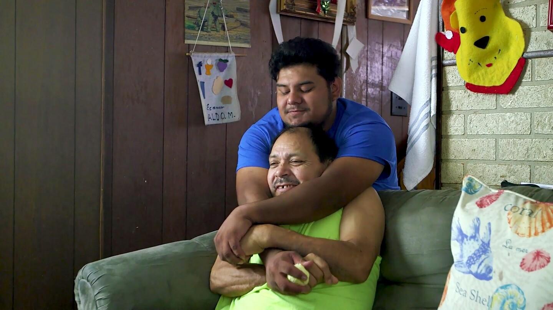 DACA student Aldo hugs his dad from behind. | Presente Films