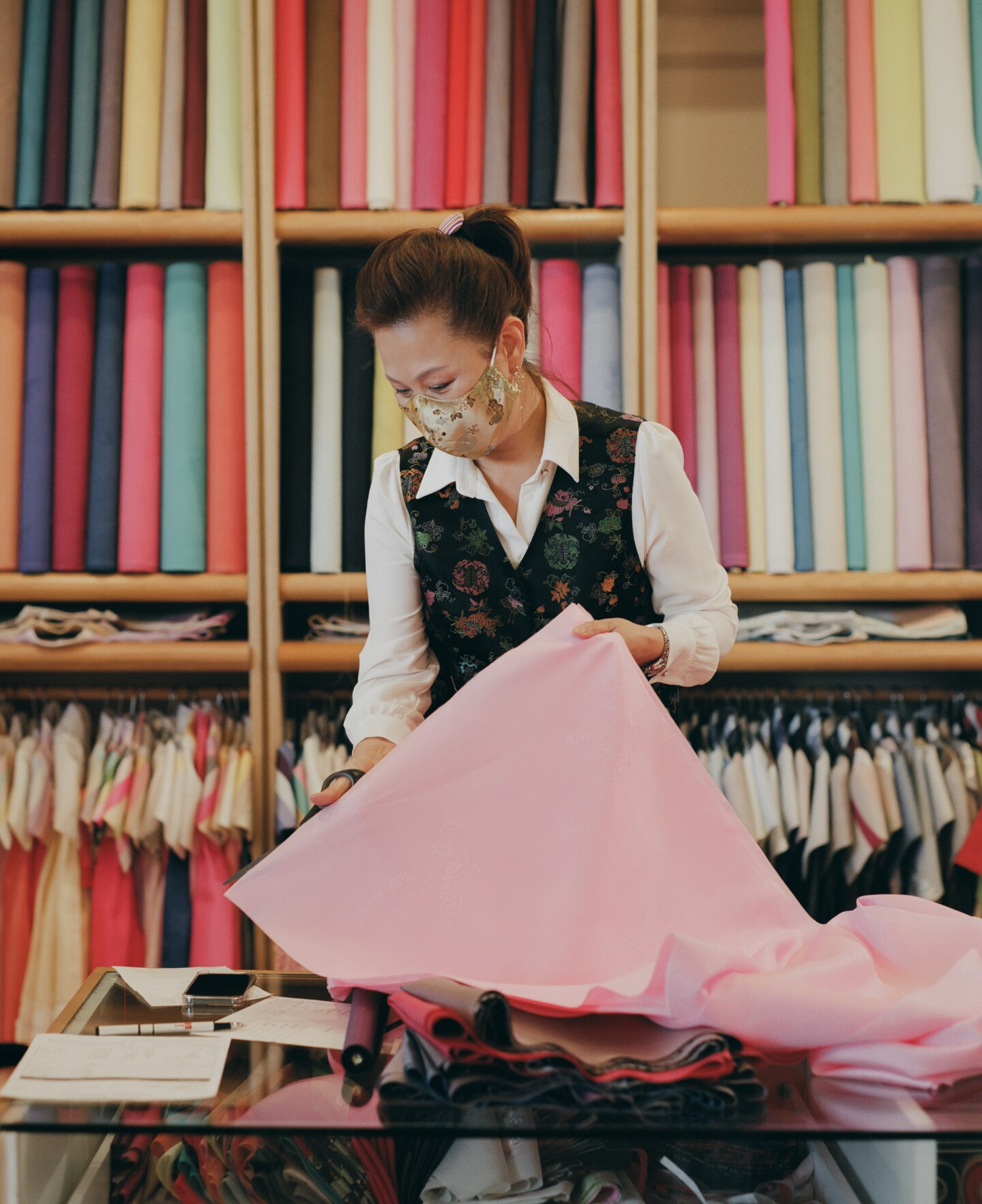 Laura folds a piece of fabric in her shop.