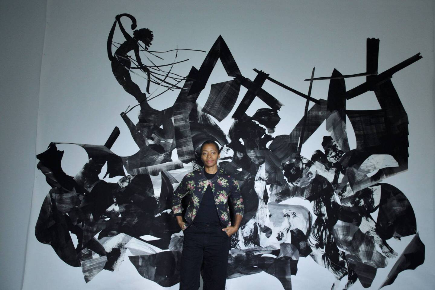Artist Kara Walker stands in front of a large, abstract black and white painting