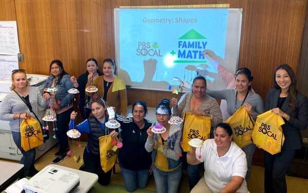A group of caregivers hold their completed shape mobiles.