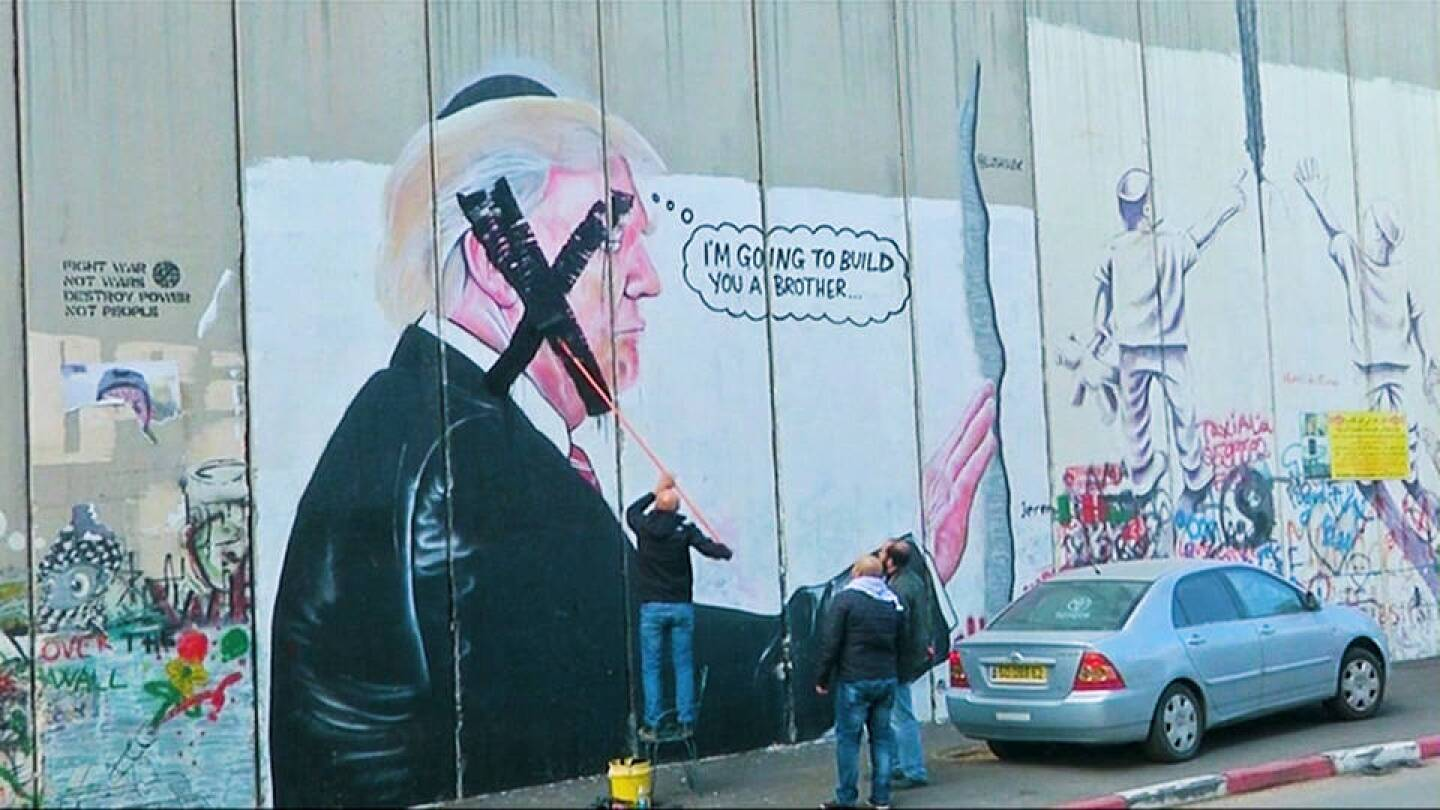 Palestinians painting over a Trump mural in protest. | Democracy Now