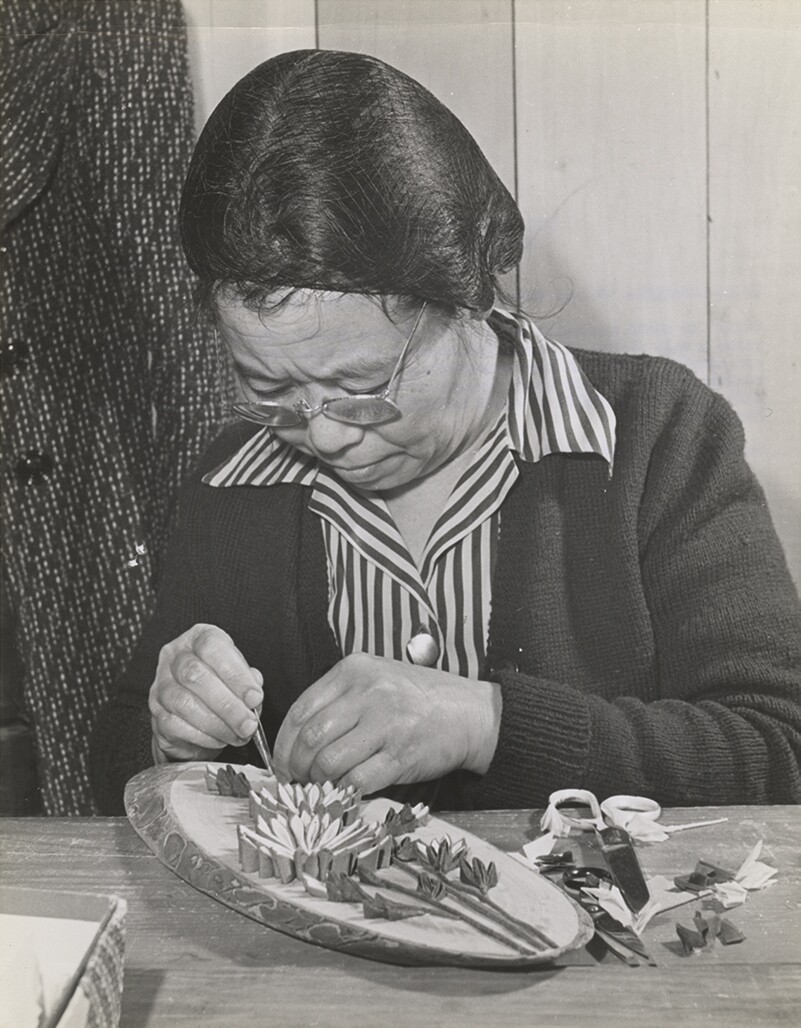 A housewife prepares a wall plaque of artificial flowers made from tissue paper. | Tom Parker, courtesy of Japanese American National Museum (2015.100.173a) ABs10 MMD