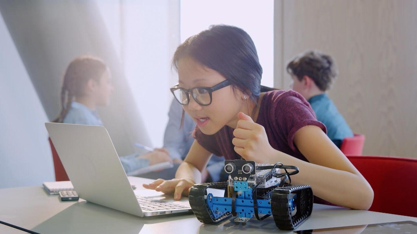 A girl browses her laptop with a robotic mechanism next to her.