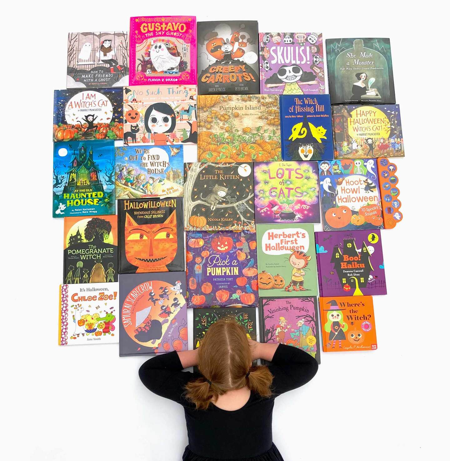 View of a little girl from above as she looks over 23 books arranged on the floor.