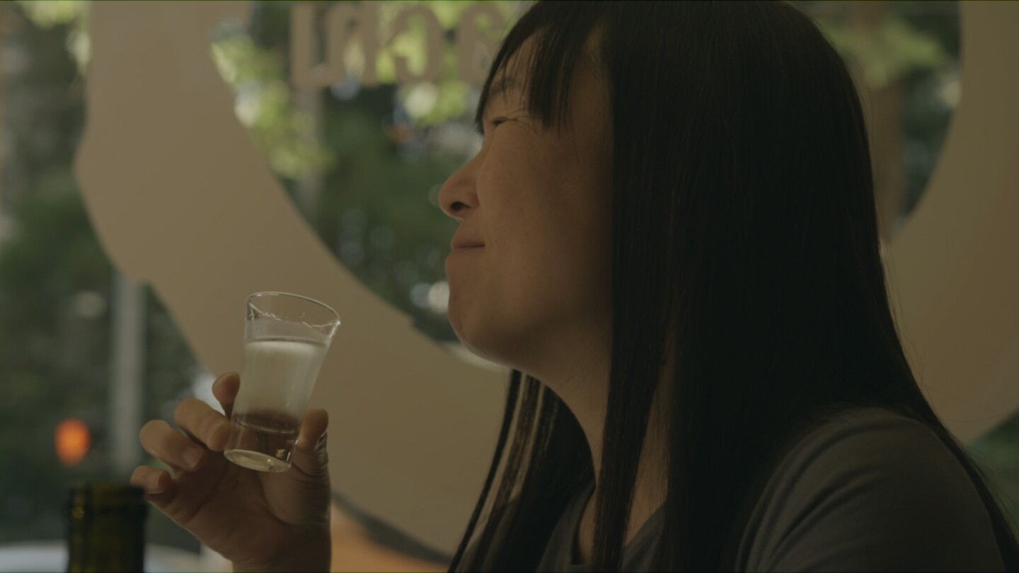 "Noriko Kamei enjoying sake | Still from ""The Migrant Kitchen"" Sequoia Sake"