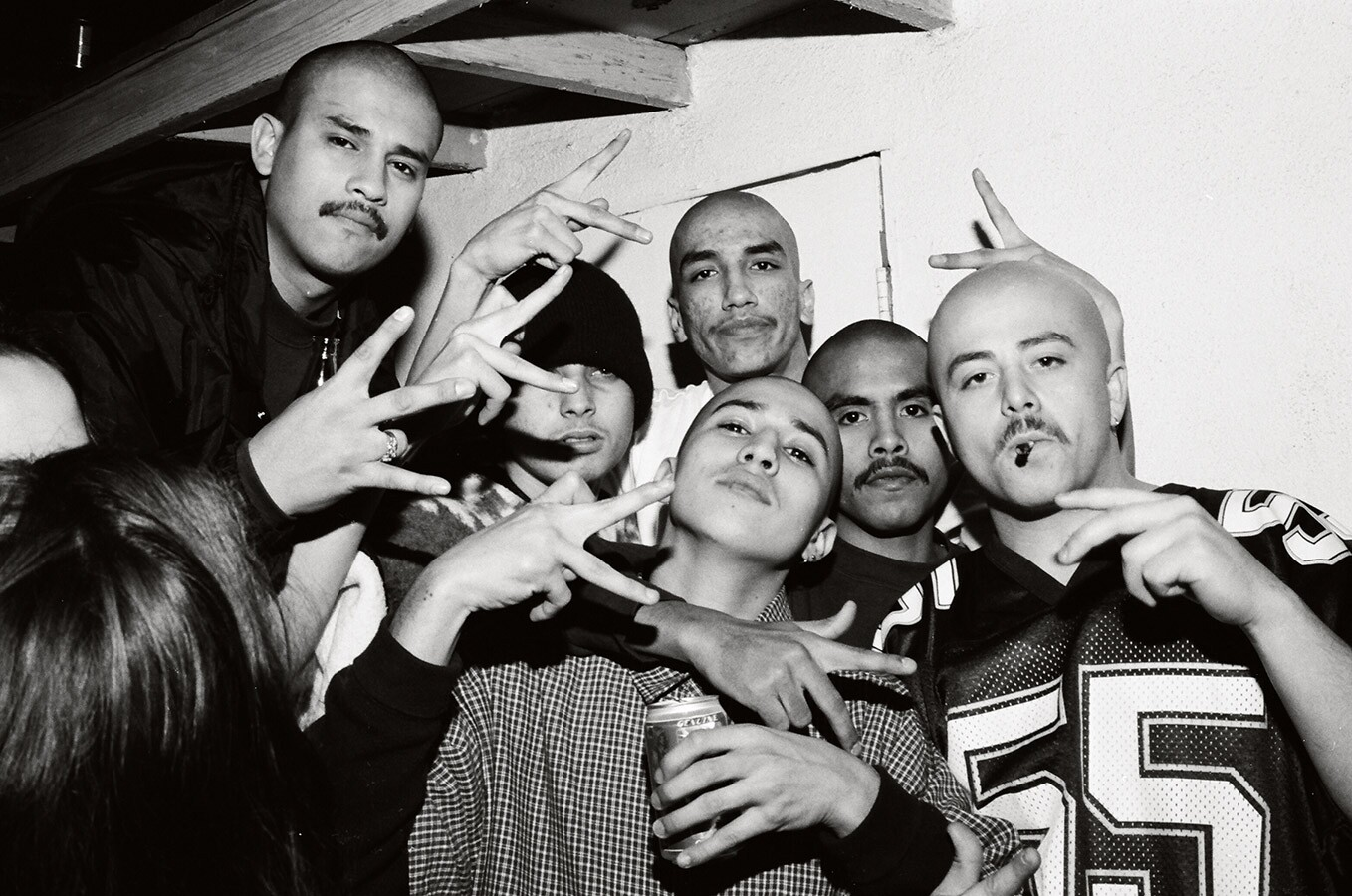 Young men at a party with gang signs
